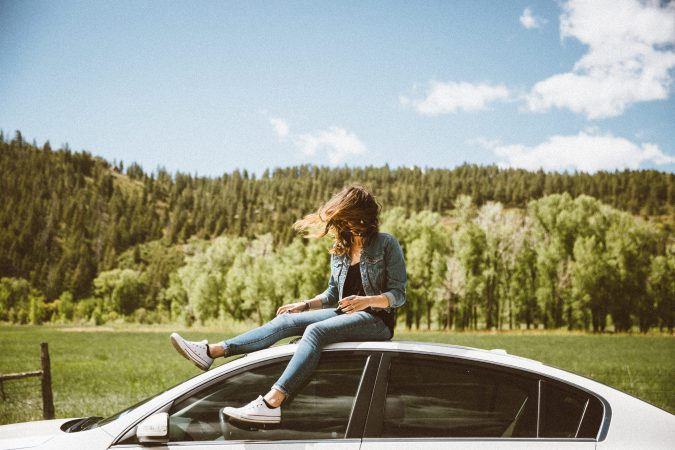 girl on top of car